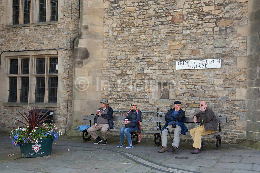 Richmond is a market town and the centre of the district of Richmondshire. Historically in the North Riding of Yorkshire, it is situated on the edge of the Yorkshire Dales National Park. North Yorkshire, England, UK. Local people sitting outside on benches at Trinity Church Square.