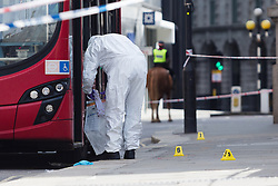 © Licensed to London News Pictures. 24/07/2016. LONDON, UK.  A forensic officer gathers evidence from the bus at the scene. A 26 year old man was stabbed outside Bank Tube station in Threadneedle Street near the Bank of England in the early hours of this morning. The man is then reported to have staggered onto the N242 bus, horrifying passengers. Ambulance and police emergency services were then called.  Photo credit: Vickie Flores/LNP
