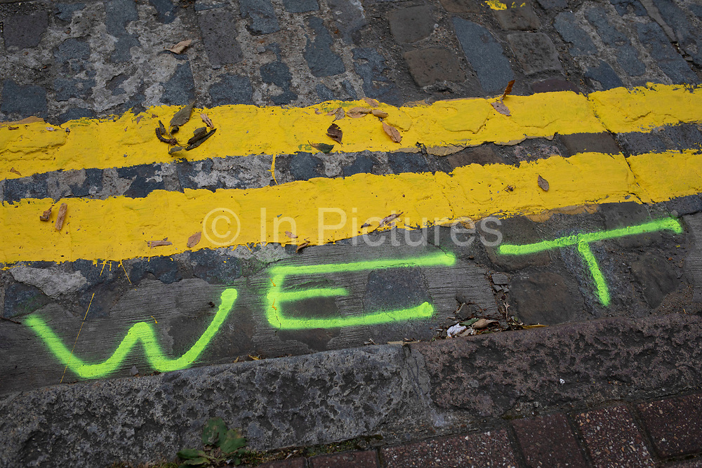 Wet paint sign on a newly painted double yellow line in London, England, United Kingdom.