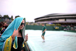 A spectator shelters under a towel as rain stops play on day three of the Wimbledon Championships at the All England Lawn Tennis and Croquet Club, Wimbledon.