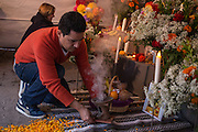 New York, NY, October 31, 2013. Juan Carlos Aguirre, Executive Director of Mano a Mano, adds copal to a censor in front of the altar. On All Saints' Day, El Dia de los Muertos, or the Day of the Dead, offerings are placed on an altar in remembrance of deceased family and friends.