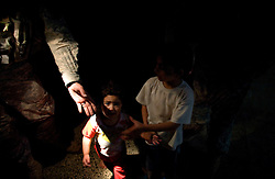 A soldier with Charlie Co. 1-26 Infantry 1st Infantry Division reaches for the hand of a young girl during a daytime raid in a darkened apartment building in central Adhamiya on Thursday April 27, 2007. The raid, which was led by Iraqi soldiers, netted three suspected IED triggermen.