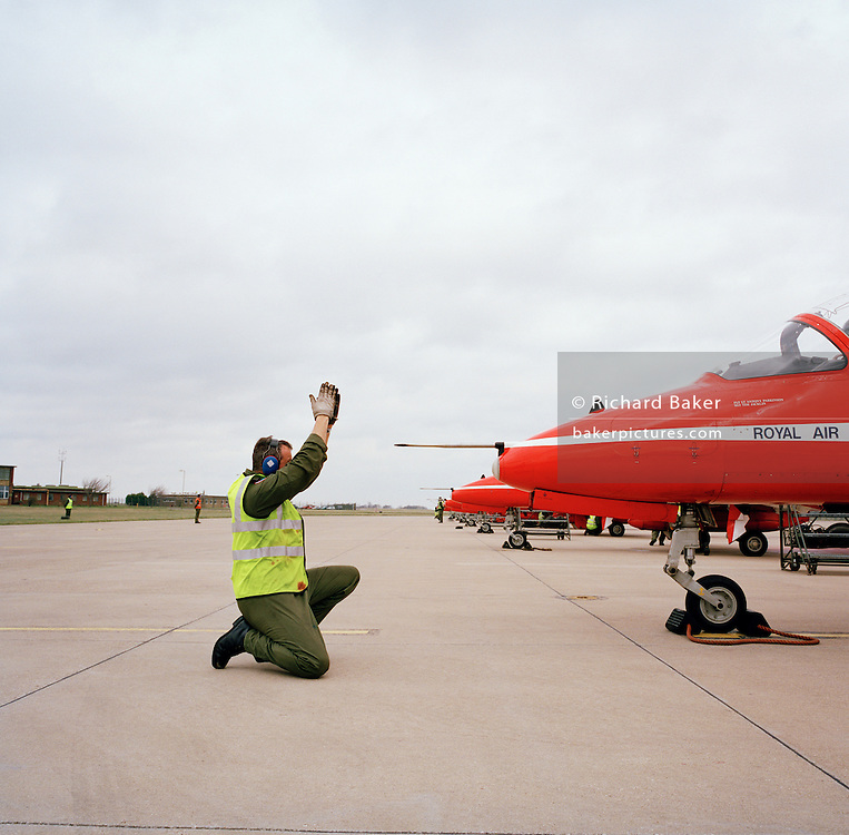 An engineer ground staff team member signals to a pilot of the Red Arrows, Britain's RAF aerobatic team.