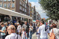 August 13, 2017 - Gdansk, Poland - People looking for goods at a flea market during 757th edition of St. Dominic's Fair are seen in Gdansk, Poland on 13 August 2017  More than one thousand 1000 traders, artists and collectors participate in the Fair occupying with their stands several streets in the centre of the in the historical city centre. St. Dominic's Fair is the largest open-air trade and cultural event in Poland and one of the largest such events in Europe. It has enjoyed over seven hundred fifty years of tradition; it was established by the Pope Alexander IV in 1260. (Credit Image: © Michal Fludra/NurPhoto via ZUMA Press)