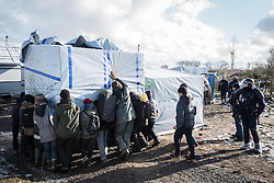 © London News Pictures. Calais, France. 07/03/16. Volunteers carry a shelter out of the demolition area under the watch of French riot police. French authorities are evicting and demolishing the southern half of the Calais 'Jungle' camp, which charities estimate to contain 3,500 people. . Photo credit: Rob Pinney/LNP