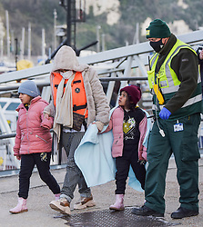 © Licensed to London News Pictures. 14/04/2021. Dover, UK. A female migrant and two children are helped ashore by a Border Force officer at Dover Harbour in Kent after crossing the English Channel. Home Secretary Priti Patel has pledged an overhaul of asylum seeker rules, with refugees having their claim assessed based on how they arrive in the UK. Photo credit: Stuart Brock/LNP