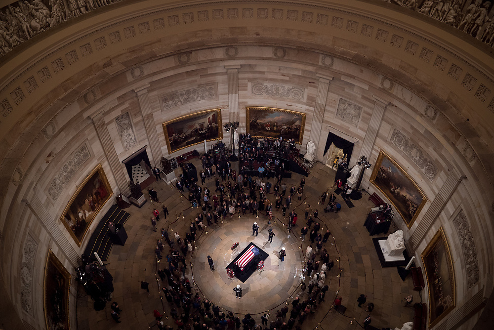 """Former President George H.W. Bush lies in state at the U.S. Capitol Rotunda on Dec. 3, 2018. The U.S. Capitol played host to a hushed stream of mourners, paying their respects to former President George H.W. Bush, whose flag-draped casket, attended by a military honor guard, laid in the center of the building's rotunda. Among some of the who paid their respects, there was a sense of longing for the """"kinder, gentler"""" nation that Bush spoke of during his inaugural address.<br /> <br /> Credit: Cameron Pollack for NPR"""