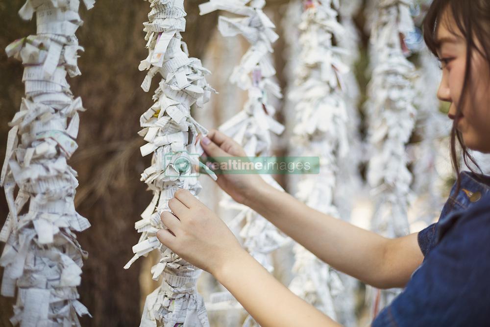 August 4, 2017 - Young woman wearing blue dress tying omikuji fortune telling paper at Shinto Sakurai Shrine, Fukuoka, Japan. (Credit Image: © Mint Images via ZUMA Wire)