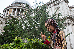 London, UK. 23rd October, 2021. Little Amal, a giant puppet of a Syrian refugee girl fleeing conflict, walks from St Paul's Cathedral to the Globe Theatre. The 3.5-metre puppet, which is nearing the end of an 8,000km journey from the Turkish-Syrian border to Manchester in support of refugees, climbed the steps of St Paul's Cathedral to present a wood carving of a ship at sea from St Paul's birthplace at Tarsus in Turkey to the dean.