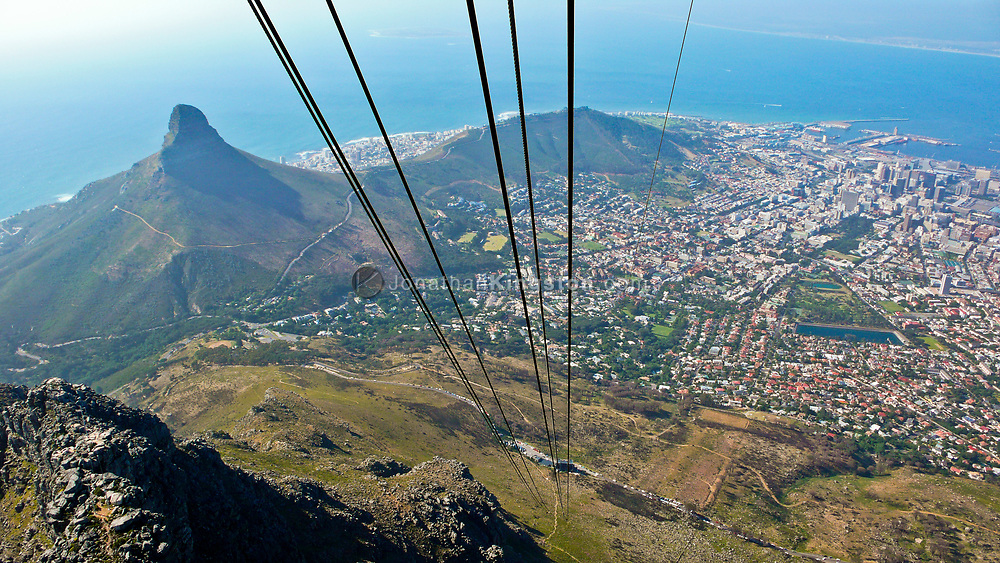 Steep cable car lines descending from Table Mountain with Lion's Head, the waterfront and Cape Town in view. South Africa.