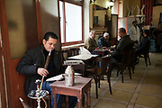 A man smokes a shish pipe at the Telegraph Cafe, off Halim Square, Cairo, Egypt