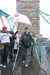 © licensed to London News Pictures. London, UK 29/04/2012. Claire Lomas, who was paralysed from the chest down after an accident, walking the London Marathon with a robotic suit to raise money for Spinal Research. On her 8th day of Marathon walk, she passes Tower Bridge under heavy rain (29/04/12). Photo credit: Tolga Akmen/LNP