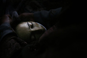 A caretaker wraps around the face with a linen belt as Qamar, a 26-year-old tuberculosis patient, dies after suffering from postpartum complications for almost two weeks at Faizabad Provincial Hospital, Faizabad in Badakshan province, Afghanistan, Sunday, May 20, 2007.