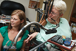 Woman with Cerebral Palsy with mouth-operated computer remote control system which operates door, television, lights etc, with Social Worker.