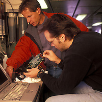 USA, Oceanography researcher works on underwater electronics on R/V Thomas G. Thompson in North Pacific Ocean
