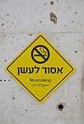 Yellow, NO SMOKING sign in Hebrew and Arabic on a concrete wall
