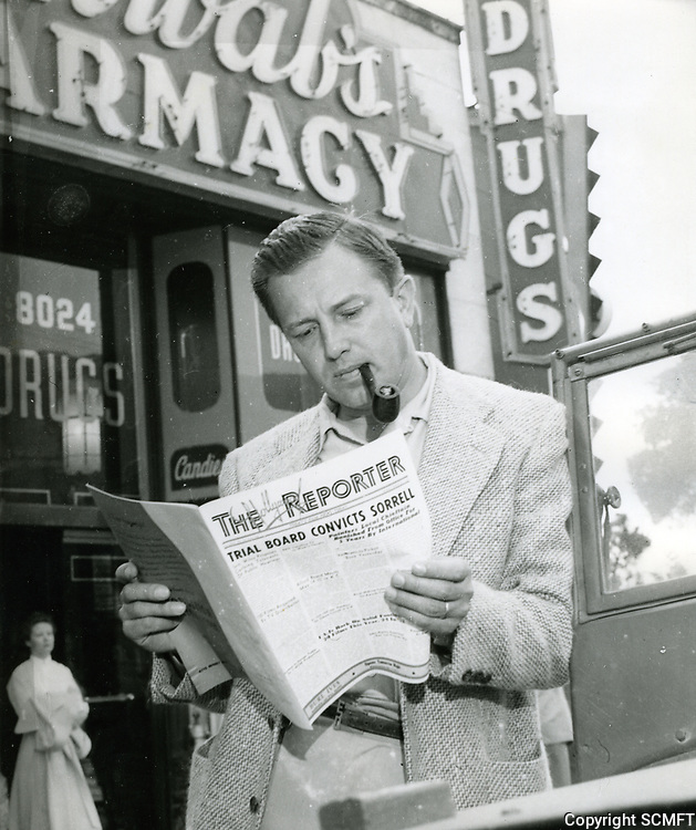 """1952 Edward Dmytryk reads the """"Hollywood Reporter"""" in front of Schwab's Pharmacy"""