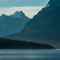 Morning mist rises over Bow Lake in Banff National Park, Alberta, Canada. Behind are (L to R)  Mount Hector and Bow Peak.