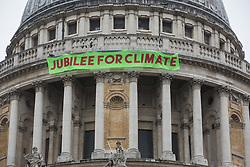 London, UK. 15th October, 2021. Activists from Africans Rising UK drop a banner from St Paul's Cathedral on the anniversary of the assassination of the Pan-Africanist President of Burkina Faso Thomas Sankara to launch the Jubilee for Climate Campaign. The Jubilee for Climate Campaign is an umbrella campaign both for the cancellation of debts for which Sankara fought so hard as well as for progressive and unifying policies to tackle the climate crisis which amplify voices from the Global South.