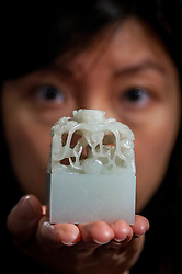 """© Licensed to London News Pictures. 03/11/2016. London, UK. An Imperial pale celadon jade Qing dynasty """"Ziqiang Buxi"""" seal, est. GBP500-700k is shown at the preview of Chinese artworks entitled """"Treasures Of The Song & Qing Dynasties"""" to be auctioned at Sotheby's in November.  Made of white jade, the seal has a knob in the shape of coiled dragons.  Photo credit : Stephen Chung/LNP"""
