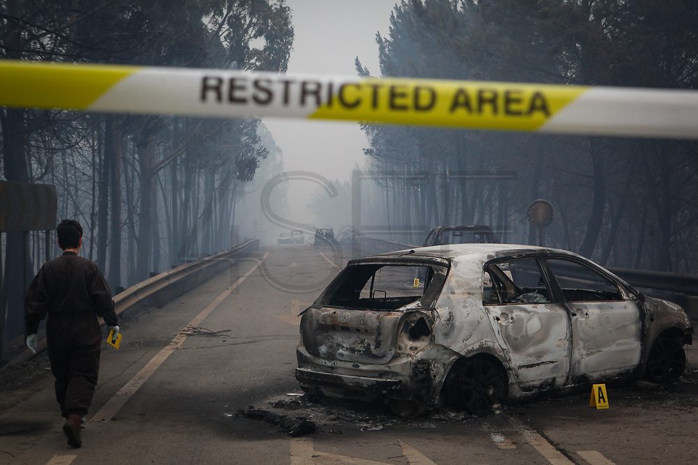 Refrigerated truck of portuguese Civil Protection arrives to carry the bodies of the dead near the burned cars at N236 road between Figueiro dos Vinhos and Castanheira de Pera, Pedrogao Grande, 18 june 2017. At least sixty two people have been killed in forest fires in central Portugal, with many being trapped in their cars as flames swept over a road on the evening of 17 June 2017. A total of 692 firefighters are providing assistance.