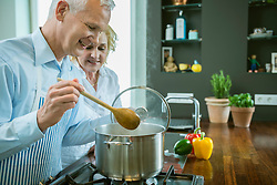 Mature couple preparing food in kitchen, smiling
