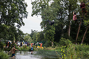 Environmental activists from HS2 Rebellion including Larch l and Swan r use a line above the shallow river Colne in Denham Country Park to attempt to protect an ancient alder tree from destruction in connection with works for the HS2 high-speed rail link on 24th July 2020 in Denham, United Kingdom. A large security operation involving officers from the Metropolitan Police, Thames Valley Police, City of London Police and Hampshire Police as well as the National Eviction Team ensured the removal of the tree by HS2 despite the protests by activists.