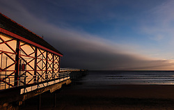 © Licensed to London News Pictures. <br /> 29/04/2016. <br /> Saltburn by the Sea, UK.  <br /> <br /> Early morning light reflects from the pier building at Saltburn by the Sea as dark storm clouds come in over the coastline. Further bad weather is expected to come down from the Arctic bringing snow and freezing temperatures to many northern and eastern parts of the country.<br />  <br /> Photo credit: Ian Forsyth/LNP
