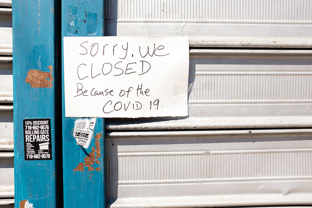 Brooklyn, NY - 26 March 2020. Residents of New York City have been asked to stay home as a result of the novel coronavirus, and all but essential businesses have been asked to close. In Brooklyn's Midwood neighborhood, many businesses have their shutters rolled down, and the few that are open limit the number of people who can enter. A sign on a closed laundromat on Avenue J.