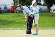 June 12 2013: Steven Alker's wife and caddie, Tanya Alker, helps him steady his hips as he practices on the putting green during the wednesday practice round at the 2013 U.S. Open hosted by Merion Golf Club in Ardmore, PA.