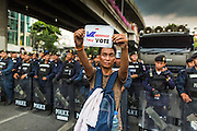 26 MAY 2014 - BANGKOK, THAILAND:  A man stands in front of riot police protesting against the coup in Thailand at Victory Monument during a pro-democracy rally in Bangkok. About two thousand people protested against the coup in Bangkok. It was the third straight day of large pro-democracy rallies in the Thai capital as the army continued to tighten its grip on Thai life.  PHOTO BY JACK KURTZ