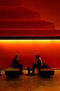 two people sitting on bench having a drink in low lighting at the Barbican art centre london