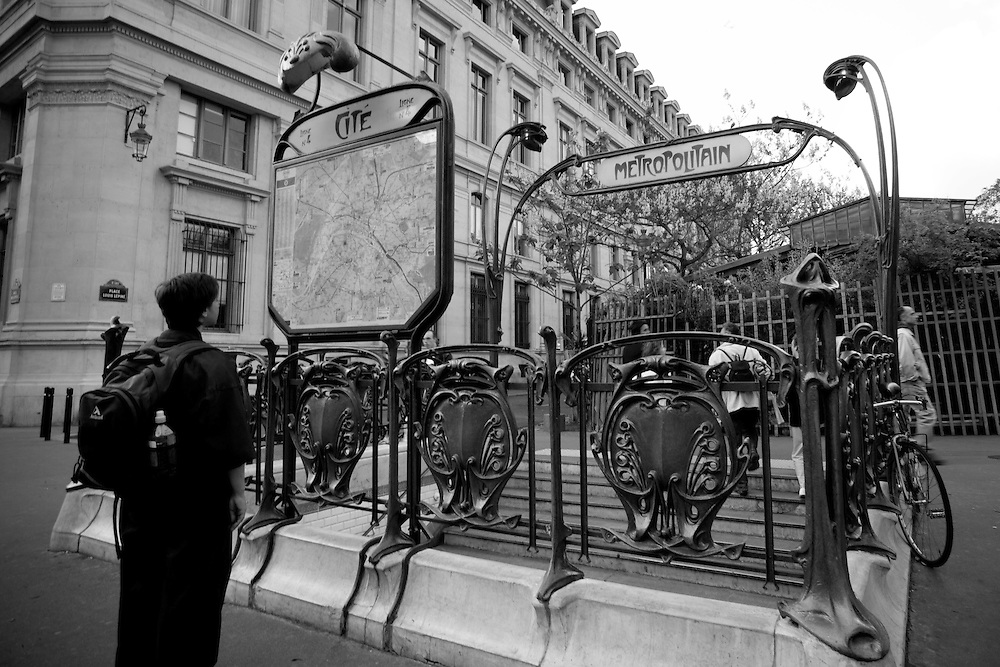 Young man, finding his way around Paris. He stands in front of the entrance to Metropolitan Line 4, Paris, France. Art Nouveau style of graceful forms in iron and glass created in turn of the 20th Century by Hector Guimard. Red glass leaf lights arched over the  stairwell. Cite map in front of entryway. One of two remaining entry-ways designed by Hector Guimard.