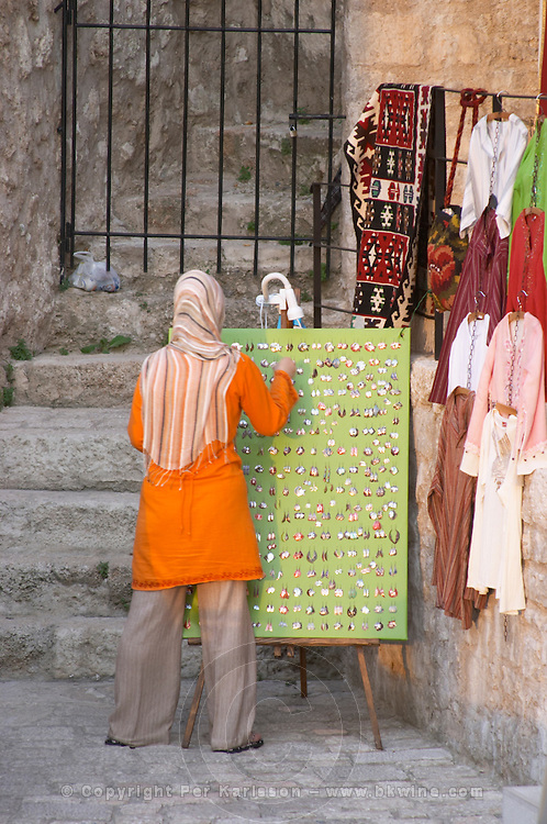 The busy old market bazaar street Kujundziluk with lots of tourist craft and art shops and street merchants. Woman in traditional Muslim clothes arranging jewelleries for sale. Historic town of Mostar. Federation Bosne i Hercegovine. Bosnia Herzegovina, Europe.