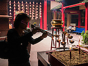 20 DECEMBER 2012 - KUALA LUMPUR, MALAYSIA: A woman lights joss sticks (incense) before praying the Guan Di Temple in Kuala Lumpur, Malaysia. The Guan Di Temple (God of War Temple) was built in 1888 and is one of the oldest Chinese Temples in Kuala Lumpur.   PHOTO BY JACK KURTZ