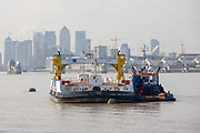 The John Burns Woolwich Ferry seen decommissioned on the River Thames in front of the Canary Wharf financial district, waiting to be towed away by the adjacent tug on October 05, 2018 in London, England on the final day of operation with the old boats.  The Woolwich ferry river crossing service closes from Saturday 6th October until the end of the year to allow new pontoons to be constructed for new boats and the ferry is planned to resume at the end of the year.