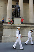 Two US Navy sailors walk past the statue of first President George Washington outside the Federal Hall National Memorial on Wall Street, New York City. A male and female personnel walk past this famous American landmark to see for themselves the site of many a notorious economic boom and crash. Federal Hall, built in 1700 as New York's City Hall, later served as the first capitol building of the United States of America under the Constitution, and was the site of George Washington's inauguration as the first President of the United States. It was also where the United States Bill of Rights was introduced in the First Congress. The building was demolished in 1812.