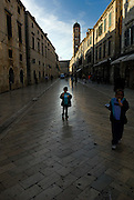 Child (5 years old) eating ice-cream cone, walking down centre of the Stradun (Placa), silhouetted against reflection of sky. Another child (9 years old) to one side. Dubrovnik old town, Croatia