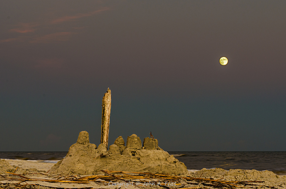 Earlier in the day, this was a spectacular sand castle.  As the sand dried and the wind picked up, it was changed to this.I love the bands of color in the sky along with the big full moon.  With nothing to give away size, this castle could be six inches or sixty feet tall!