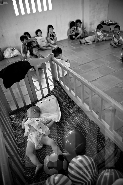 In an orphanage of Khanh Hoa province, a little baby with a diaper sleeps in a bed while young kids sit and play in the background. Vietnam, Asia