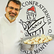 Chef Franco Favarettoholds a  plate with Baccala Mantecato in front of the sign of the brotherhood of the Baccala stands of the Biennale del Gusto on October 28, 2013 in Venice, Italy. The Biennale del Gusto is an exhibition held over four days, dedicated to traditional food and drinks from all regions of Italy.
