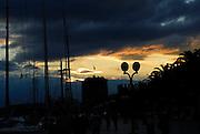 Fortress Kamerlengo, boat masts and waterfront promenade in semi-silhouette at sunset. Trogir, Croatia