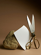 """Photograph of a rock. piece of paper and a scissors otherwise known as the game """"Rochambeau"""" on a brown background"""