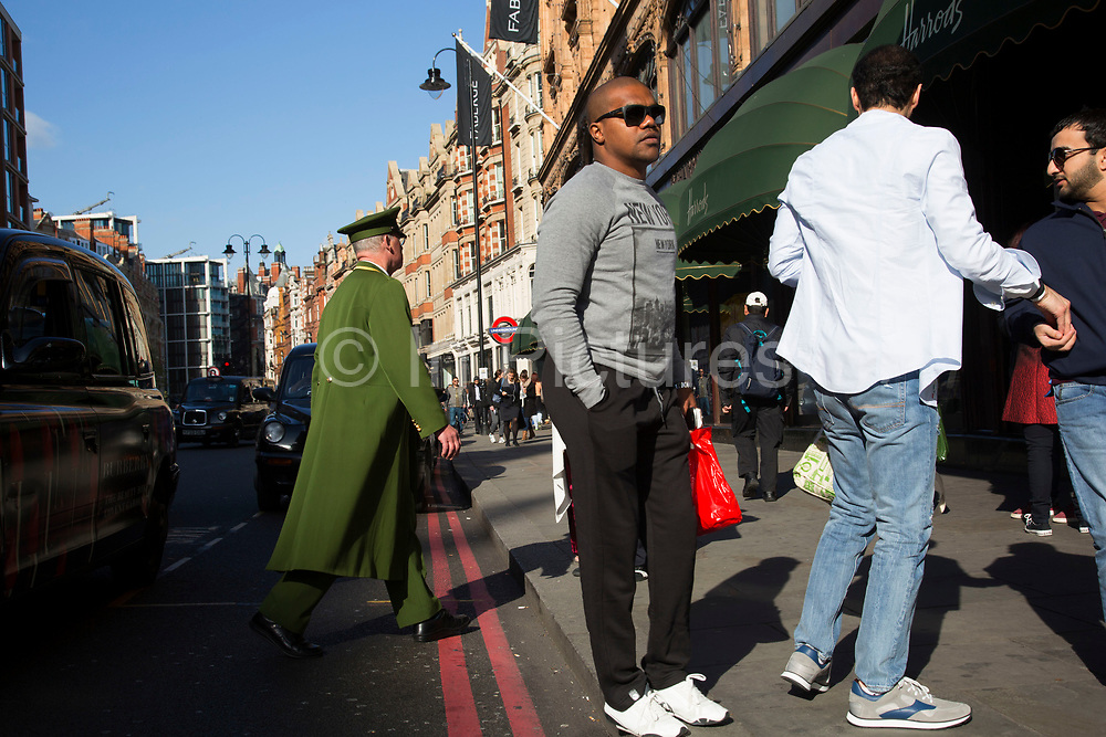 Doorman assists shoppers arriving in taxis outside Harrods department store in the exclusive area of Knightsbridge. In a selected few boroughs of West London, wealth has changed over the last couple of decades. Traditionally wealthy parts of town, have developed into new affluent playgrounds of the super rich. With influxes of foreign money in particular from the Middle-East. The UK capital is home to more multimillionaires than any other city in the world according to recent figures. Boasting a staggering 4,224 'ultra-high net worth' residents - people with a net worth of more than $30million, or £19.2million.. London, England, UK.
