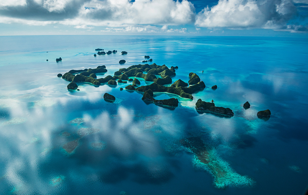 An aerial view of the rock islands of Palau. The sea is so calm it's reflecting the sky above.