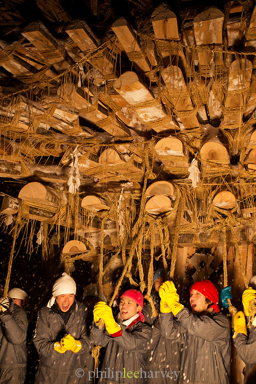 Group of smiling men standing under wooden construction, Nozawaonsen, Japan