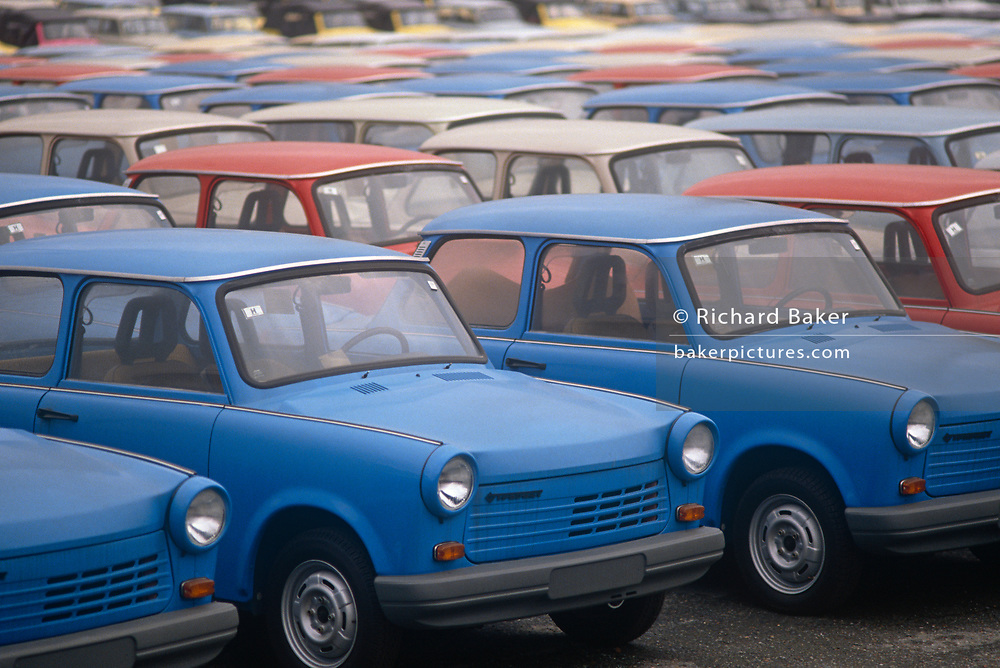 "Six months after the fall of the Berlin Wall, the last Trabant cars await buyers outside the factory production line, on 1st June 1990, in Zwickau, eastern Germany (former DDR). The DDR-produced Trabant suffered poor performance, but its smoky two-stroke engine regarded with affection as a symbol of the more positive sides of East Germany. Many East Germans streamed into West Berlin and West Germany in their Trabants after the opening of the Berlin Wall. It was in production without any significant change for nearly 30 years. The name Trabant means ""fellow traveler"" in German."