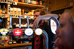 © Licensed to London News Pictures. 20/03/2020. London, UK.  Publican Aaron Chick looks on in the Pocket Watch during the government's announcement that all pubs and restaurants  will be closing tonight indefinitely, pending monthly review.  Photo credit: Guilhem Baker/LNP