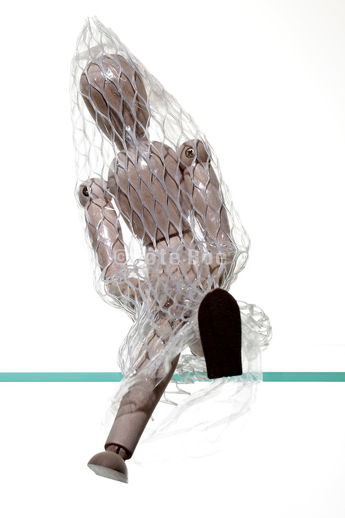 sitting wooden mannequin figure with plastic net covering