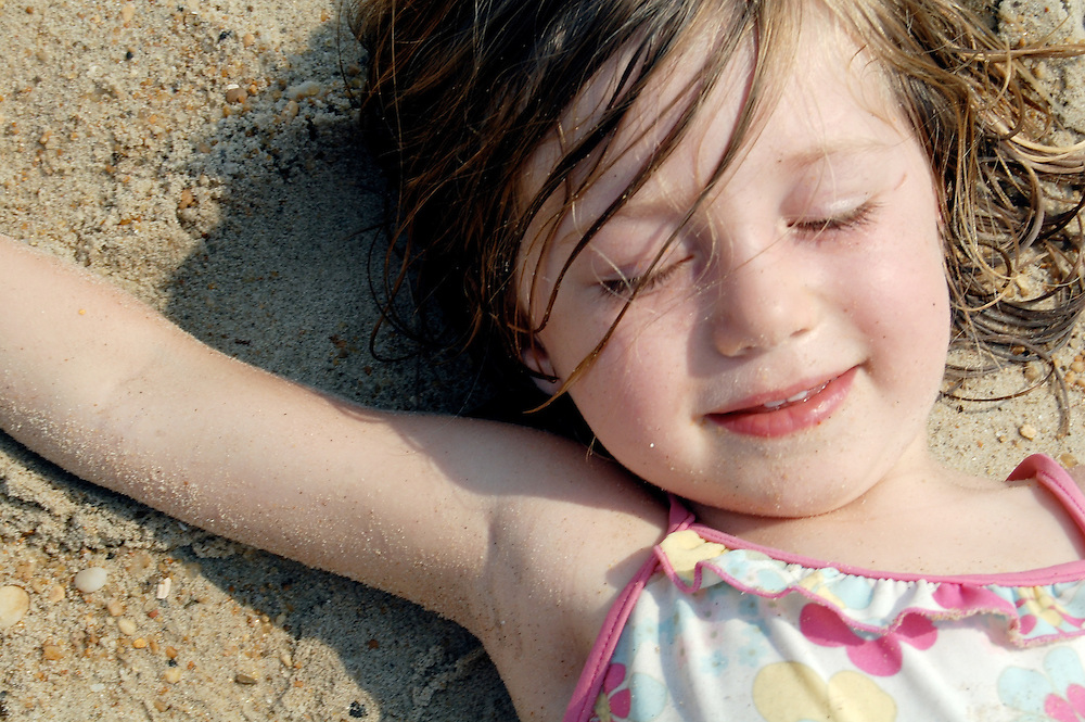 A little girl smiles in bliss with her eyes closed, and stretched out in the sun during a sandy tumble at the beach in the Outer Banks, North Carolina. To license this image, please contact Getty Images at http://www.gettyimages.com/detail/101001184/Flickr